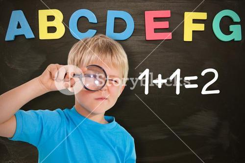 Composite image of cute boy looking through a magnifying glass
