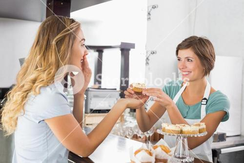 Pretty waitress serving cupcake to customer