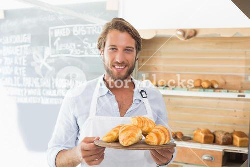 Handsome waiter holding tray of croissants