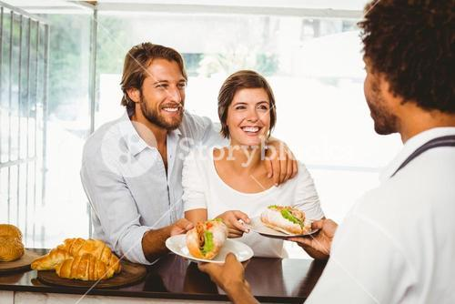 Barista serving two happy customers