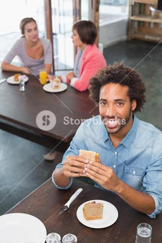 Handsome man eating a sandwich