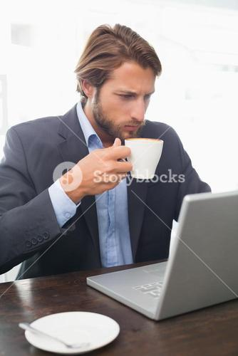 Businessman working on his laptop having coffee