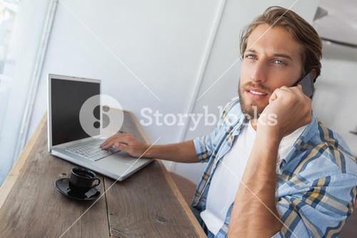 Casual man using laptop having coffee