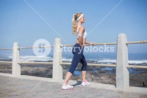 Fit woman stretching on the pier