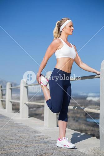 Fit blonde stretching on the pier