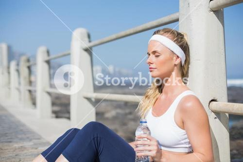 Fit blonde sitting on the pier
