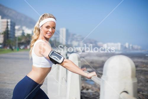 Fit blonde listening to music warming up