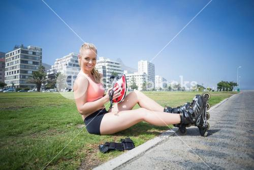 Fit blonde putting on her roller blades