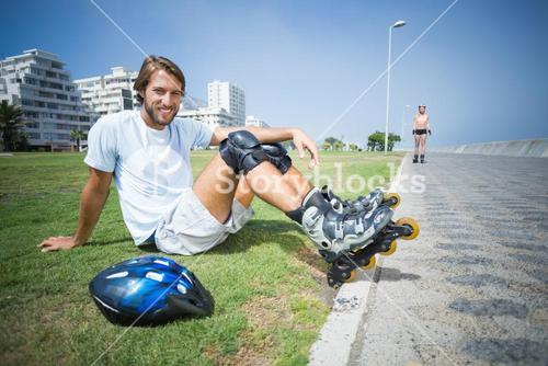 Fit man getting ready to roller blade