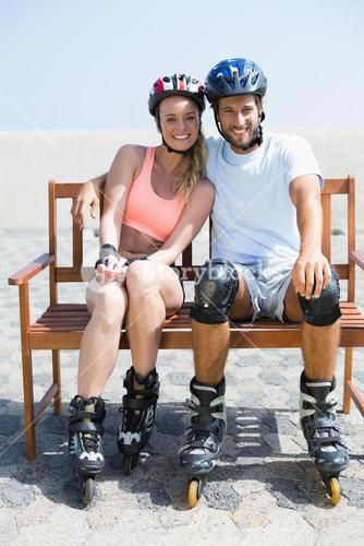 Fit couple getting ready to roller blade