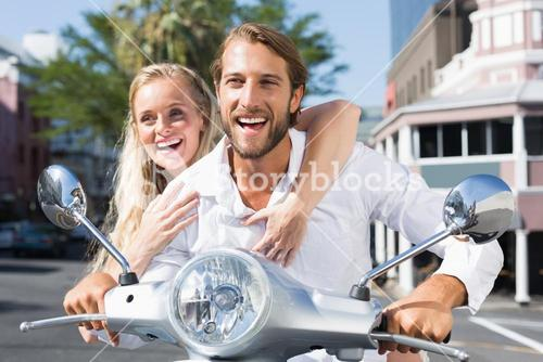 Attractive couple riding a scooter