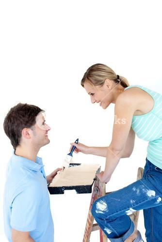 Happy couple painting a room in their new house