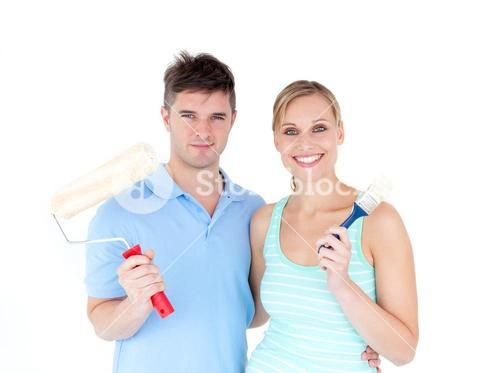 Loving couple painting a room in their new house
