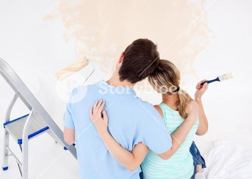 Young couple looking at a painted wall