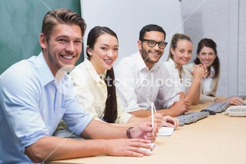 Smiling business team sitting in a line