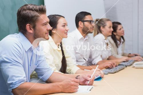 Business team sitting in a line listening during a meeting