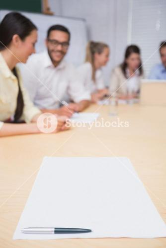 Blank page on the table in front of the business team