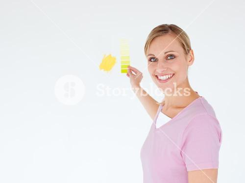 Smiling woman painting a room looking at the camera