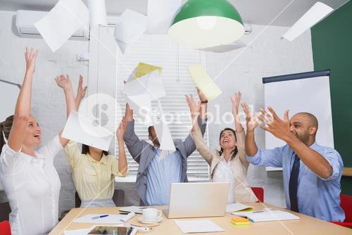 Cheerful workers throwing paper and smiling