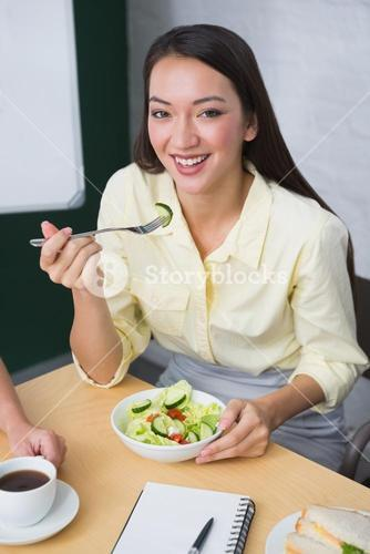 Smiling pretty businesswoman eating healthy salad