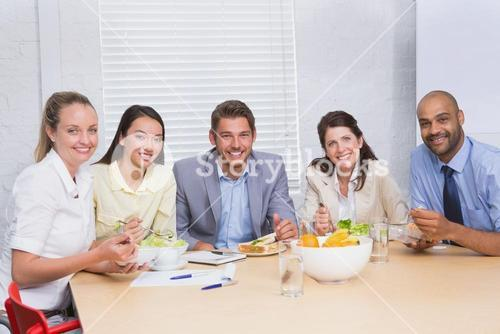 Workers smiling at camera eating sandwiches and salad