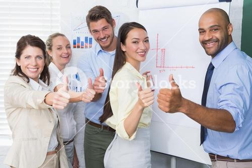 Smiling business team gesturing thumbs up in meeting