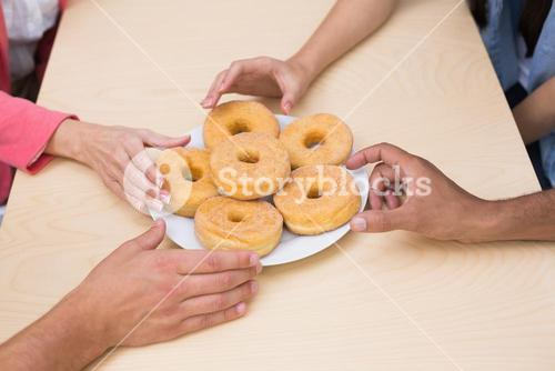 Business team reaching for doughnuts on table