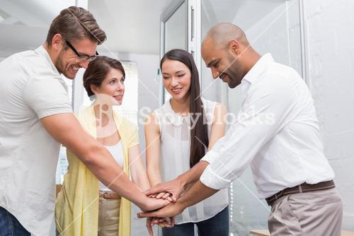Smiling business team putting their hands together