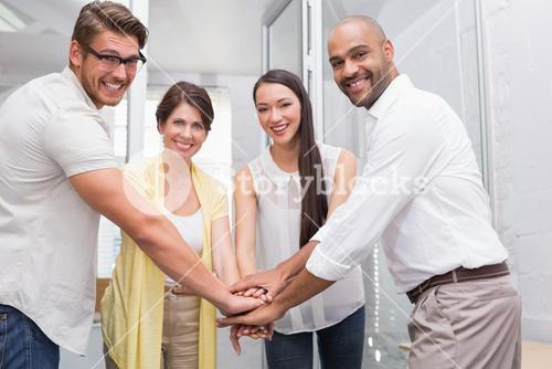 Business team putting their hands together smiling at camera