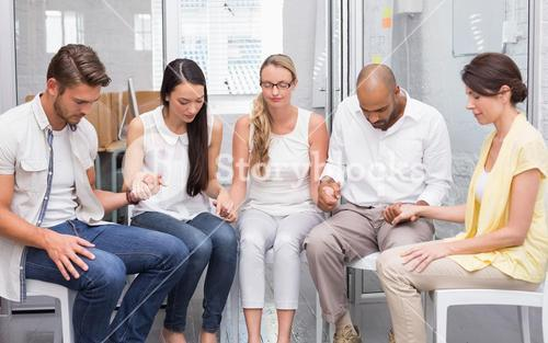 Business team holding hands while praying