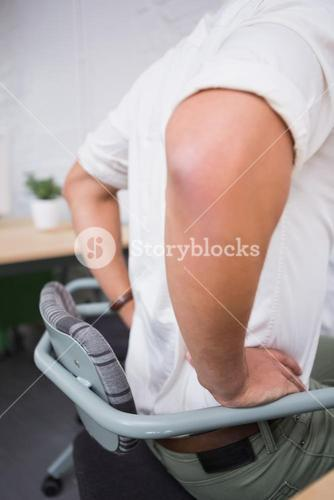 Mid section of businessman suffering from backache