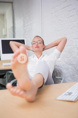 Businesswoman with legs crossed at ankle on desk