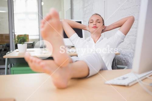 Businesswoman sitting with legs crossed at ankle on desk