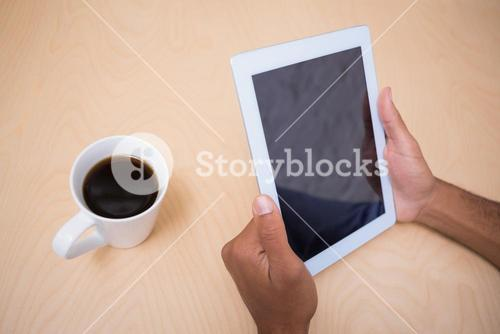 Hands holding digital tablet by coffee cup on table