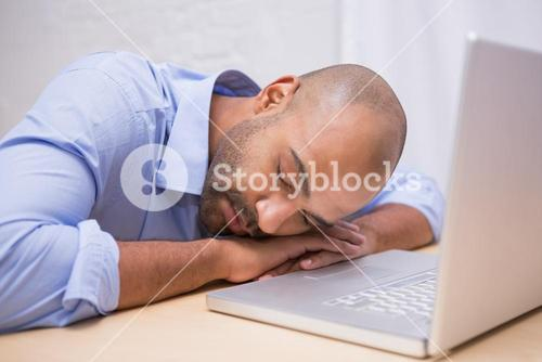 Businessman sleeping by laptop at desk