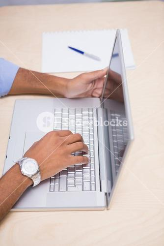 Hands using laptop at desk