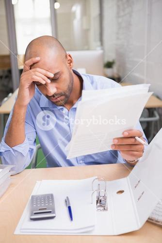 Businessman with paperwork at desk