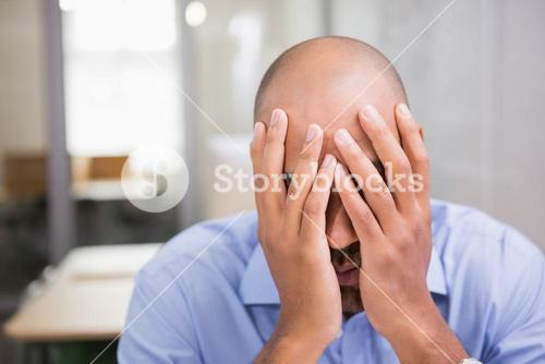 Businessman with head in hands at office