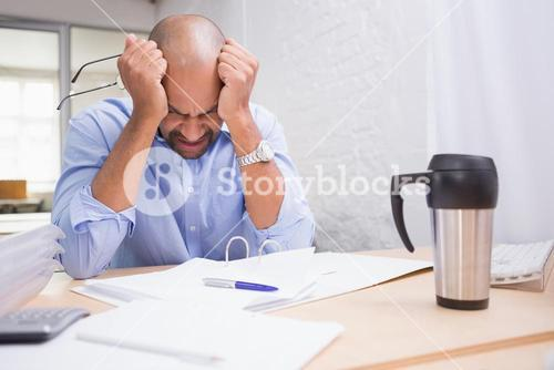 Tired businessman with paperwork at desk