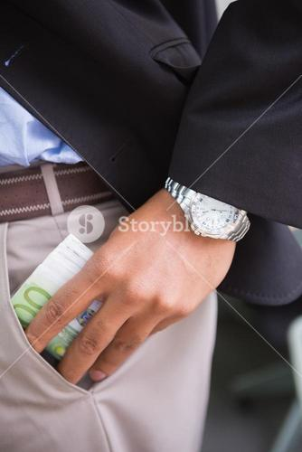 Businessman keeping currency in pocket