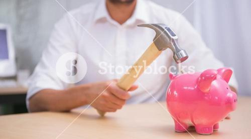 Man breaking piggy bank with hammer