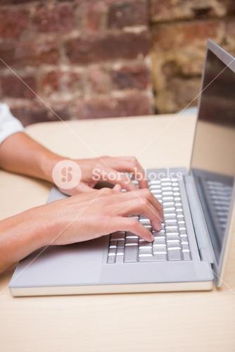 Hands using laptop at office desk