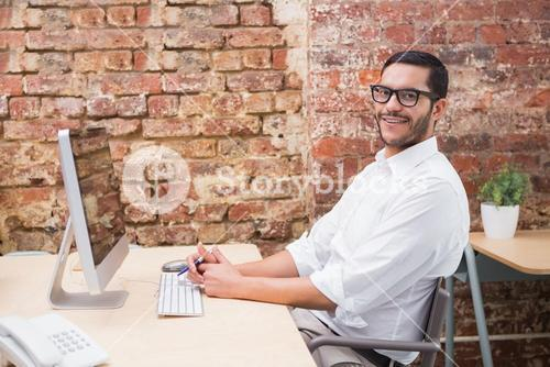 Portrait of businessman with computer at desk