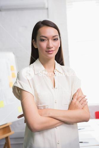 Confident businesswoman with arms crossed in office