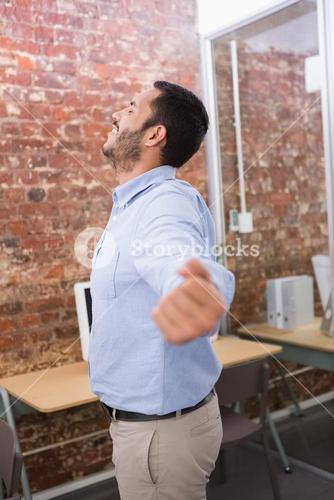 Businessman stretching hands in office