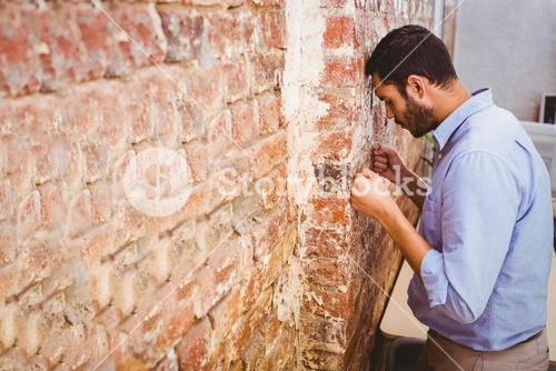 Thoughtful businessman standing against brick wall