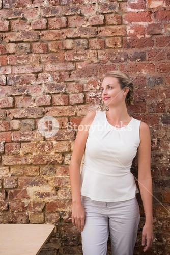 Thoughtful businesswoman against brick wall