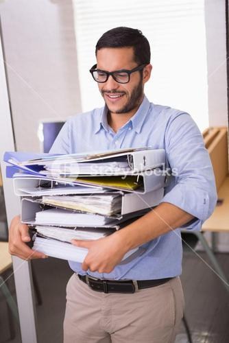 Businessman carrying stack of folders