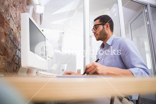 Man working at desk with computer and digitizer