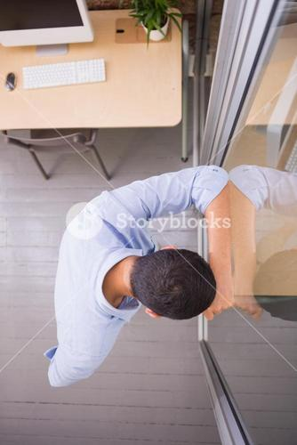 Thoughtful young businessman standing against glass wall at office
